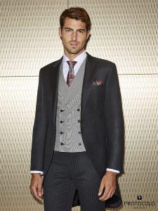 Chaqué cuna entallado gris marengo con chaleco brienz cuadro de gales con estampado floral y corbata dique fucsia.