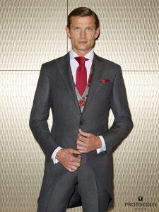 Chaqué Novio de corte Slim de color gris. Modelo Aren Buho, con Chaleco cuadro difuminado con flores estampadas y corbata fucsia.